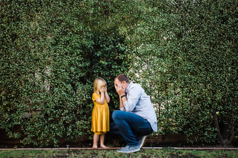father and three year old daughter playing hide and seek in the bushes waiting for mom {Oakland in-home lifestyle Family Photographer}