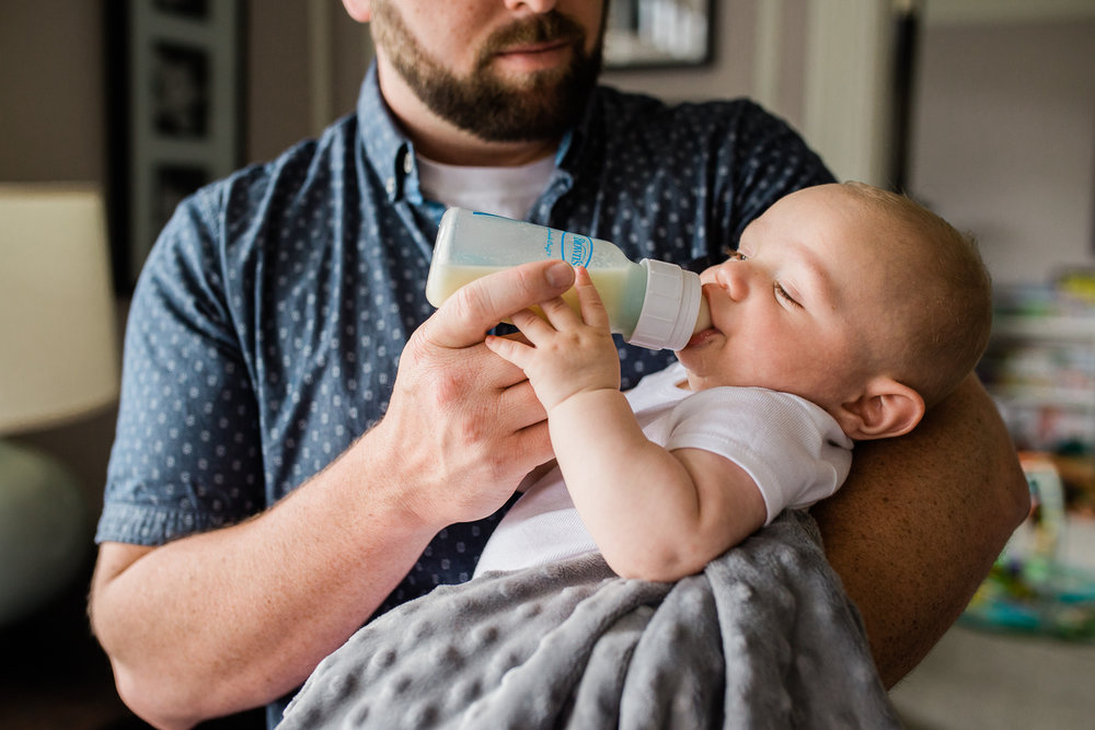 candid moment - Dad holding and giving his newborn baby boy a bottle {San Francisco in-home lifestyle newborn photographer}