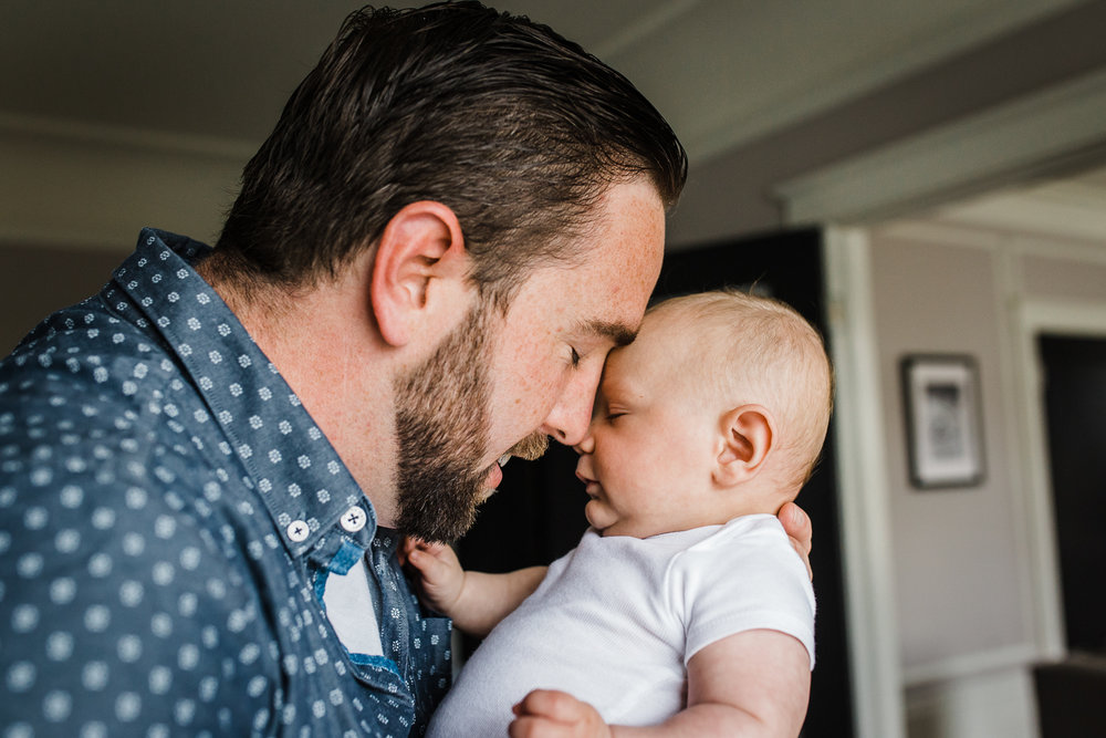 candid moment - Dad with his face close to and snuggling his newborn baby boy {San Francisco in-home lifestyle newborn photographer}