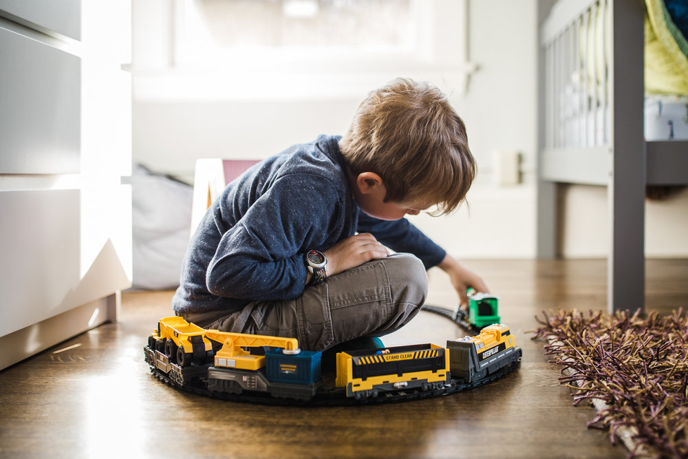 five year old boy playing with trains and sitting in the middle of a track {Oakland Child Photographer}