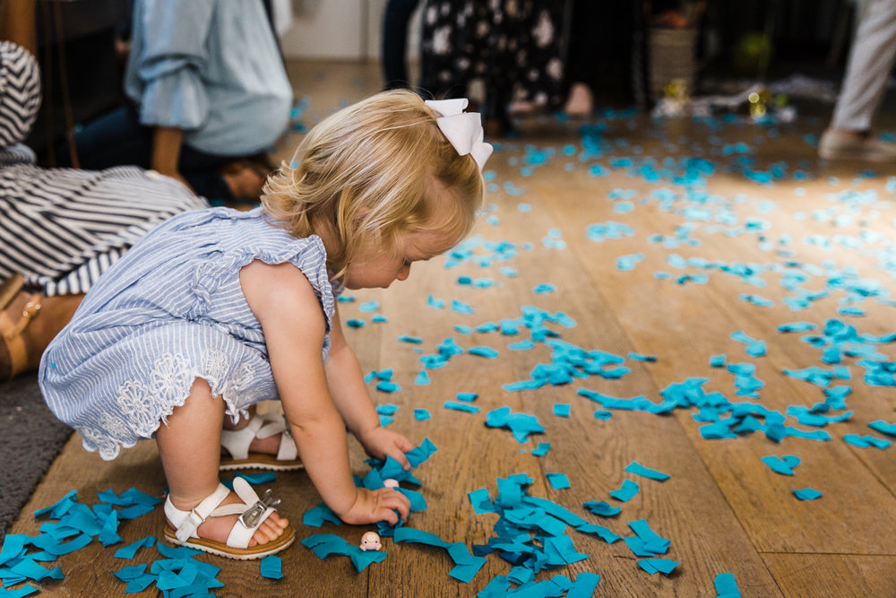 A two year old girl playing with blue confetti on the floor after a gender reveal party {San Francisco Family Photographer}