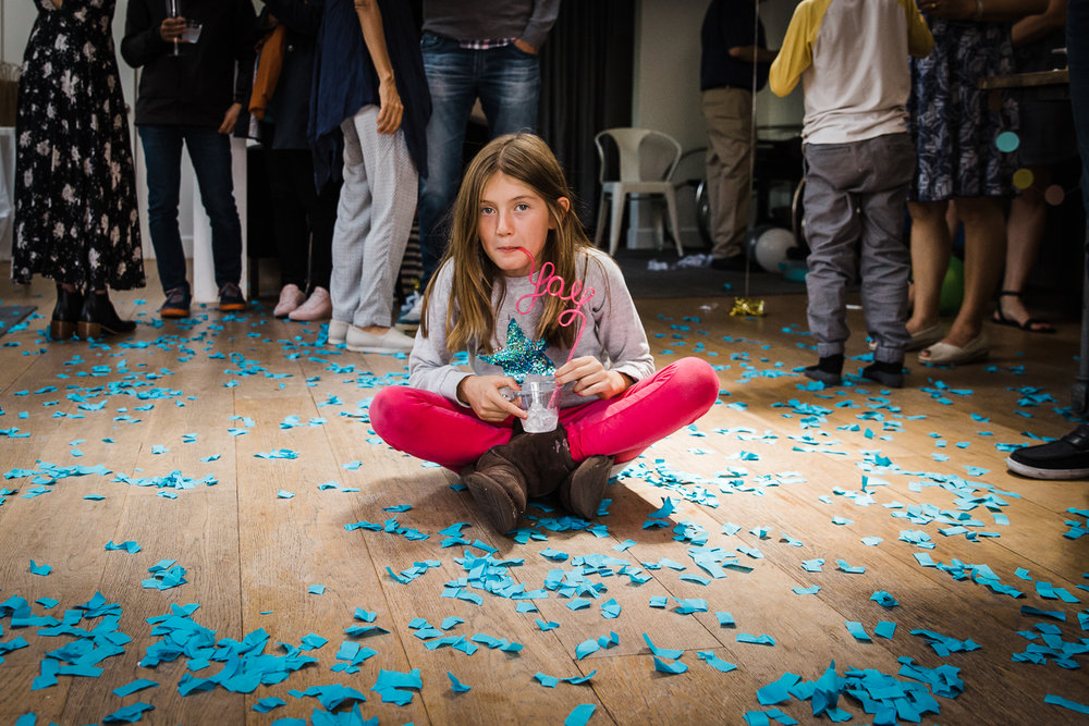 A girl sitting on the floor in the middle of blue confetti after a gender reveal party  {San Francisco Family Photographer}
