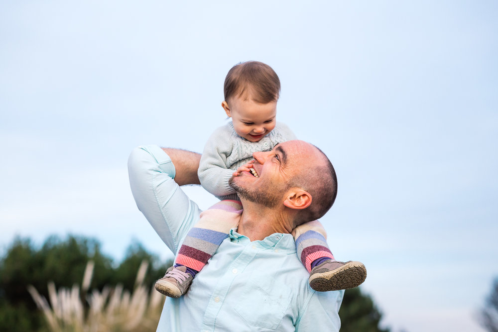Dad standing with one year old baby girl on his shoulders {East Bay Baby Photographer}