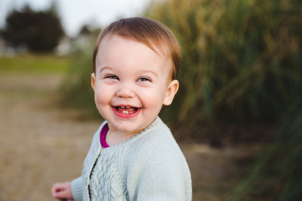 portrait of one year old baby smiling at the camera with just two bottom teeth while on the beach {East Bay Baby Photographer}