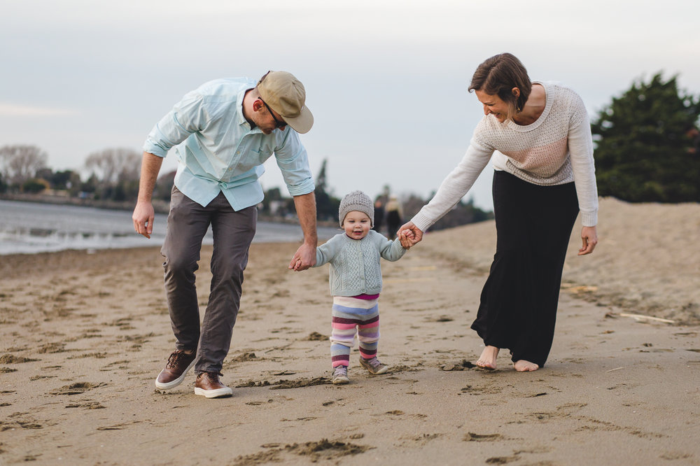 family of three all holding hands and walking down the beach {East Bay Family Photographer}