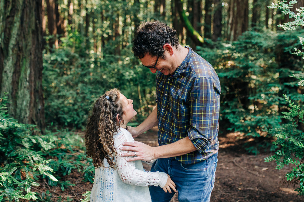 father and daughter looking at each other and smiling while playing in the woods {Oakland Family Photographer}