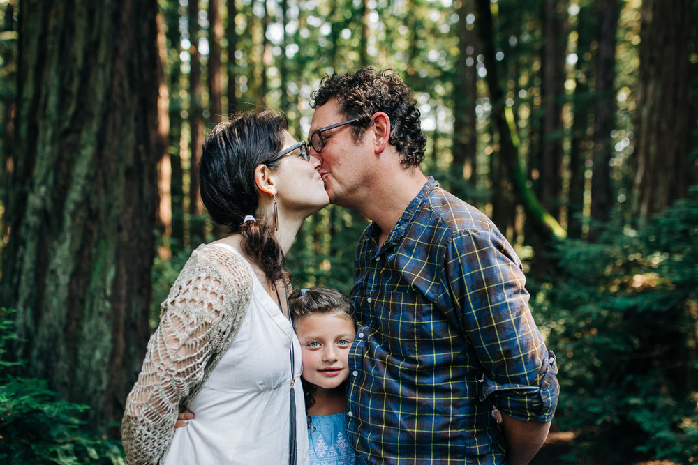 parents kissing as their eight year old daughter squeezes between them while in the woods {Oakland Family Photographer}