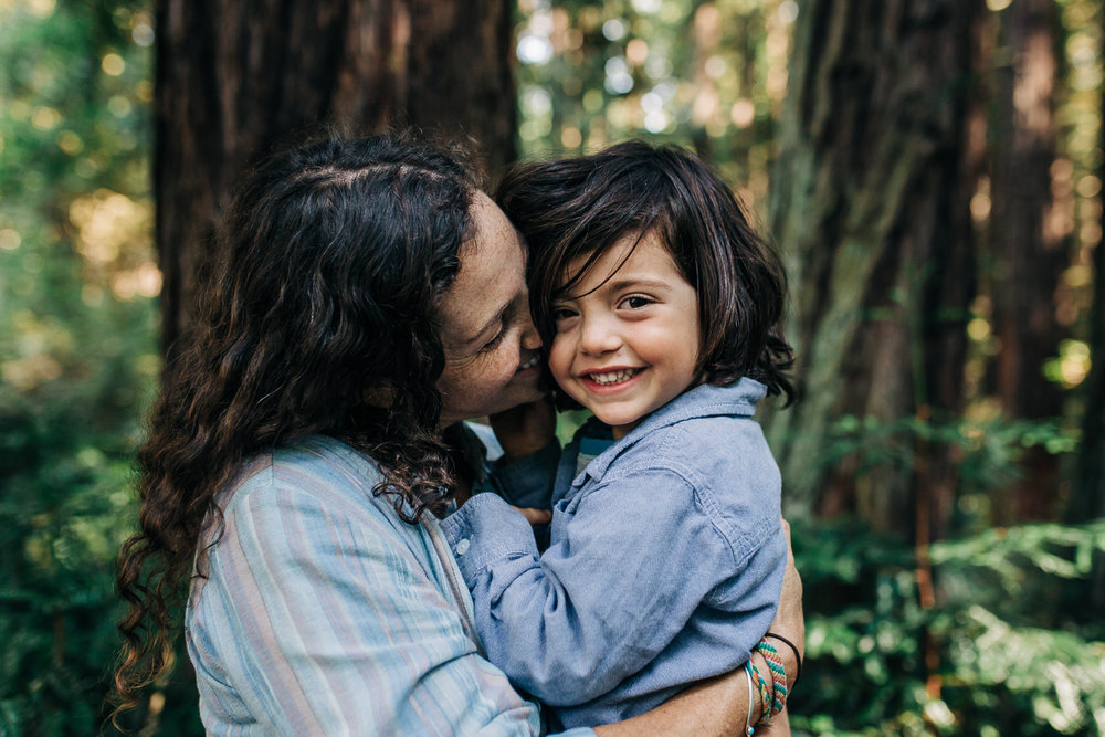 Mom snuggling her four year old boy as he looks at the camera and smiles while in the woods {Oakland Family Photographer}