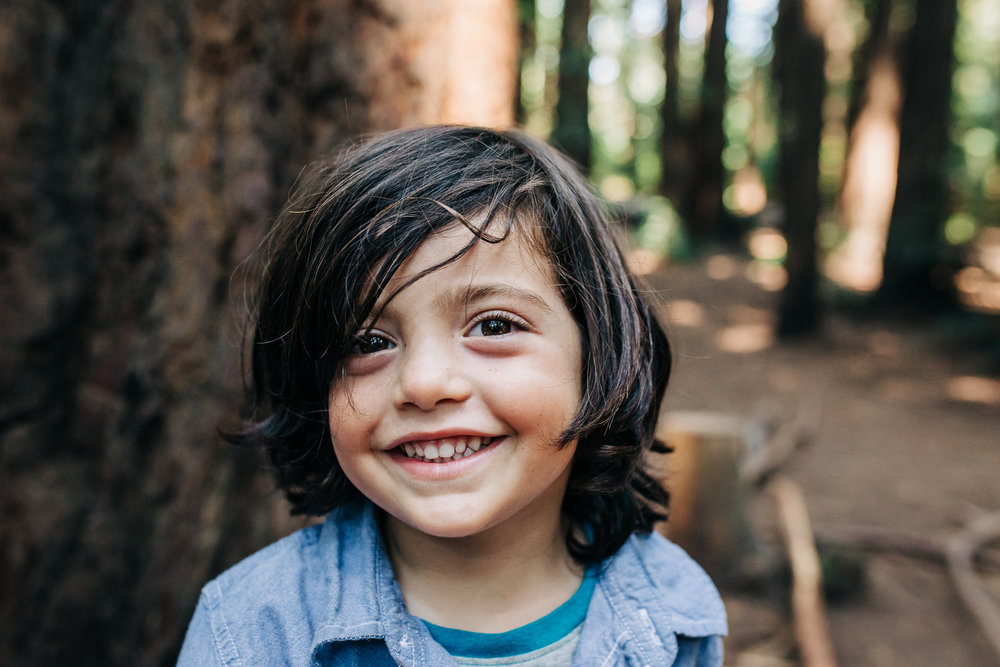 Portrait of a four year old boy looking at the camera and smiling while playing in the woods {Oakland Family Photographer}