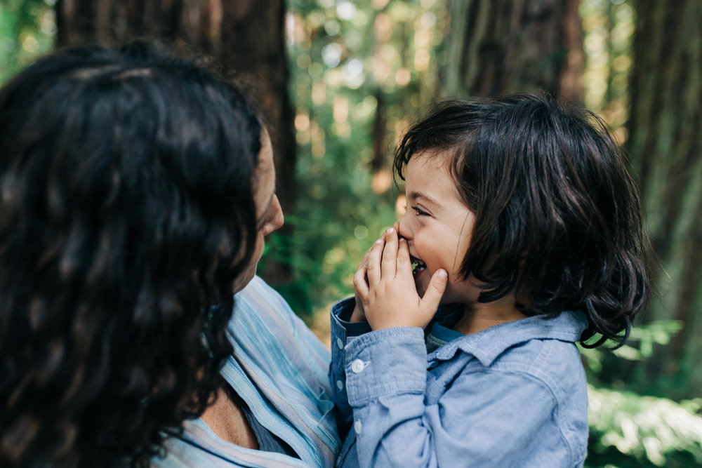 Mom holding four year old son as he looks at her and smiles while in the woods | Oakland Family Photographer