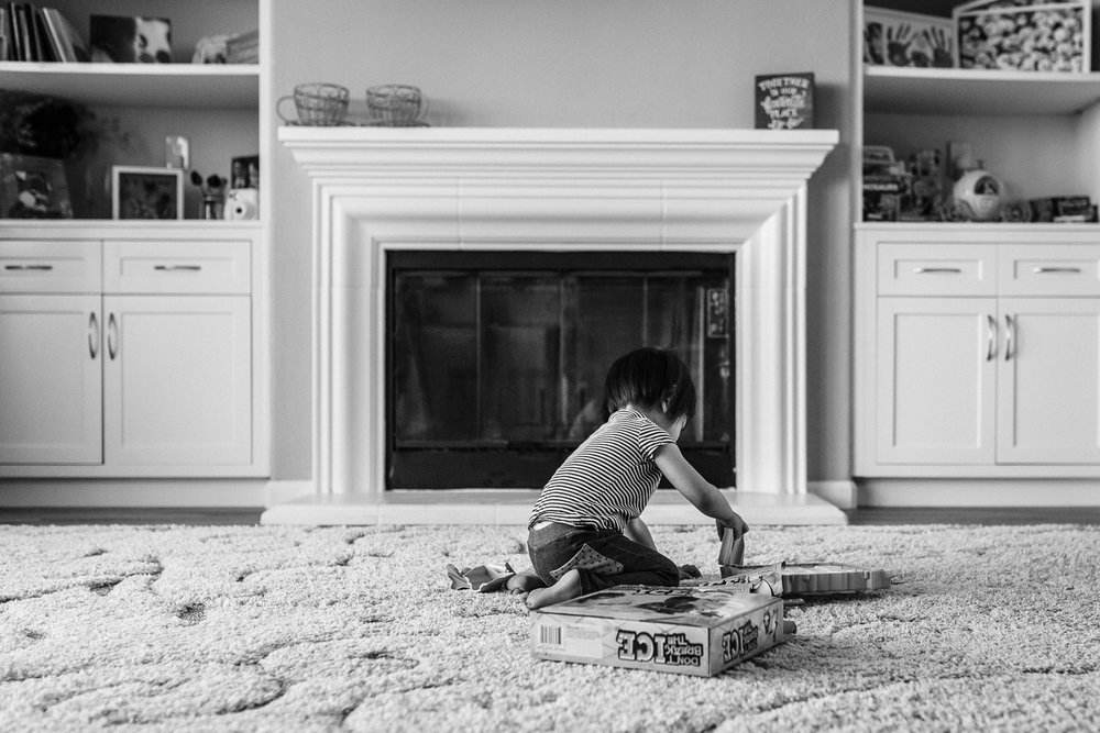 little girl sitting in front of a fireplace setting up a board game to play | East Bay Lifestyle Photographer