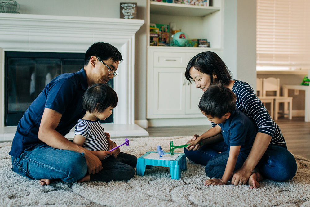family of four sitting on the floor playing a board game together | East Bay Lifestyle Photographer