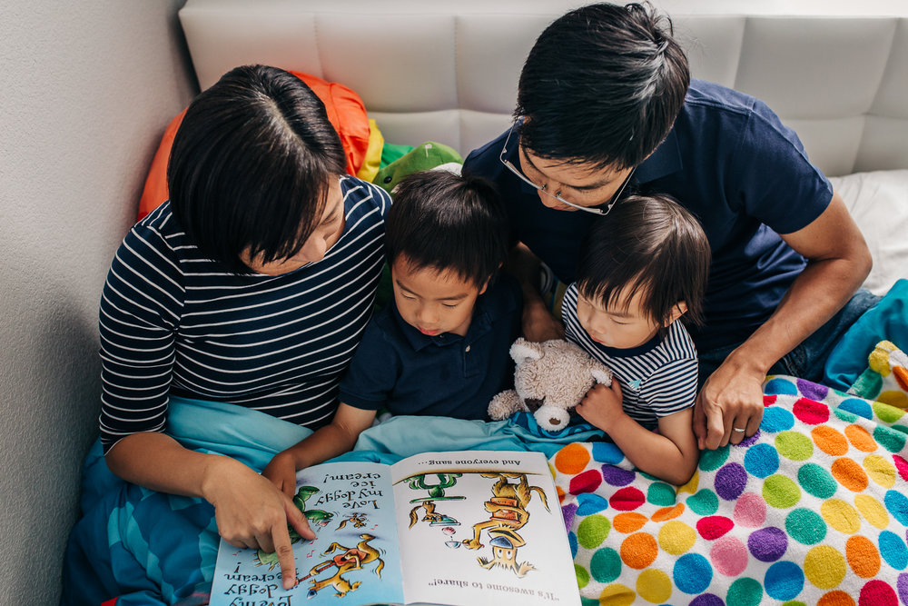birds eye view of a family reading a book together in bed | East Bay Lifestyle Family Photographer
