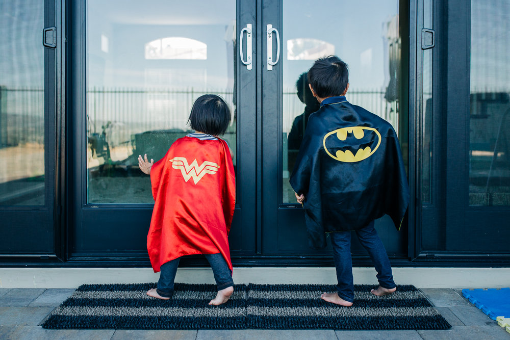 the backs of a boy and a girl wearing superhero capes as they look into sliding glass doors | East Bay Lifestyle Family Photographer