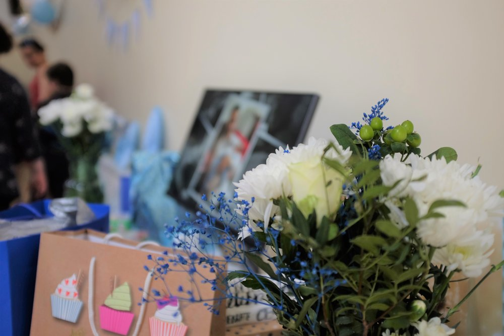 Gift table with flowers, gift bags and slideshow at the thankful naming ceremony.