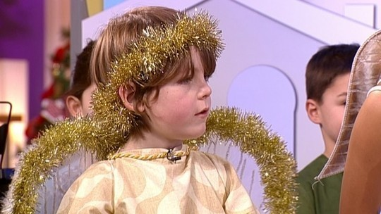 A child playing Angel Gabriel on TV wearing the traditional gold tinsel halo and wings.