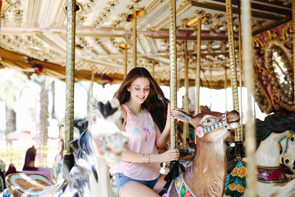 Image of girl riding a carousel horse.