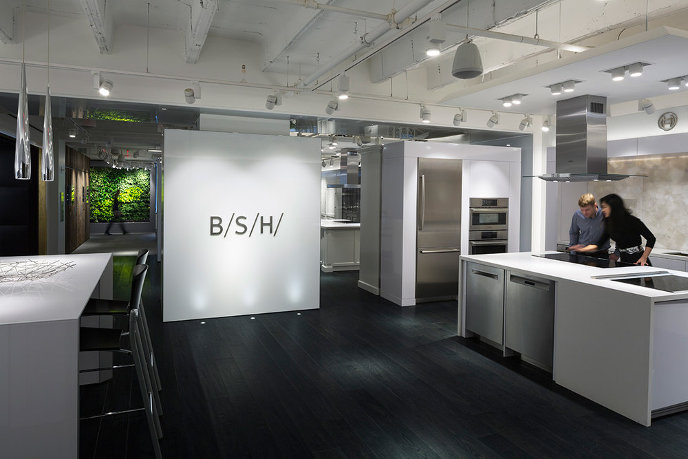 BSH logo displayed on a wall as a man and woman explore the showroom's kitchen space in New York. MEP provided by 2LS Consulting Engineering.