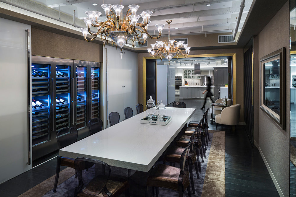Dining room display with a long white table, wine refrigerators, and chandeliers and a woman walking past. MEP designed by 2LS Consulting Engineering.