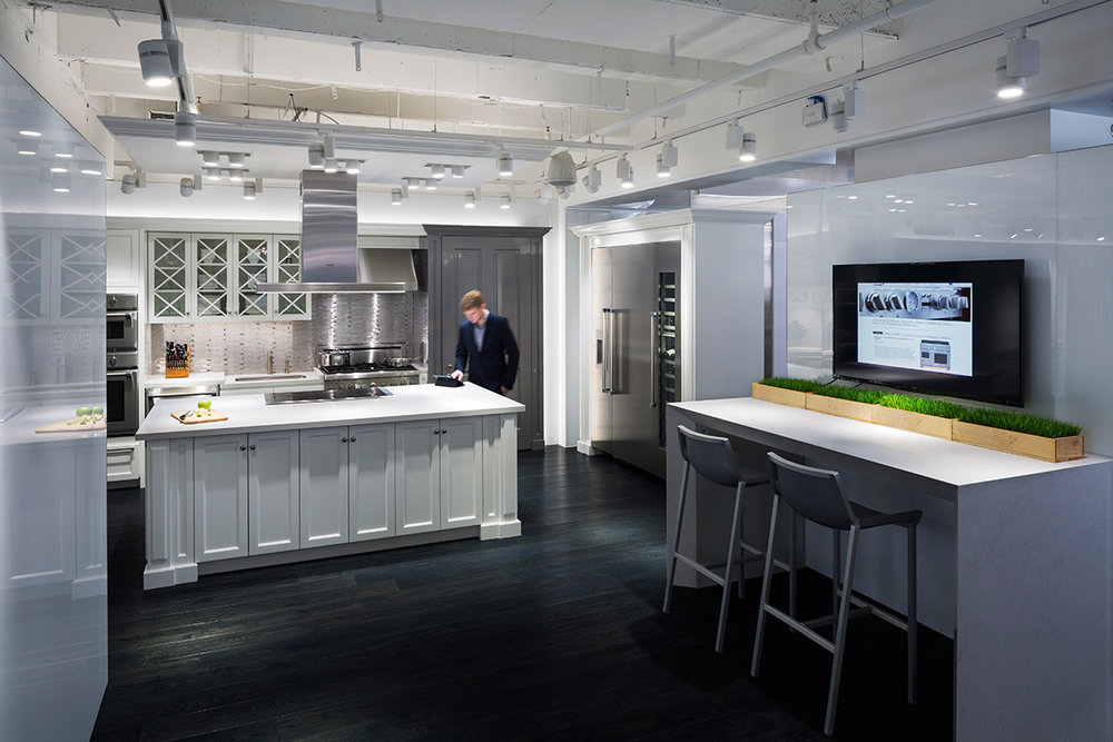 Man in a blazer viewing a tablet on a kitchen counter in the showroom of BSH, located in New York. MEP designed by 2LS Consulting Engineering.