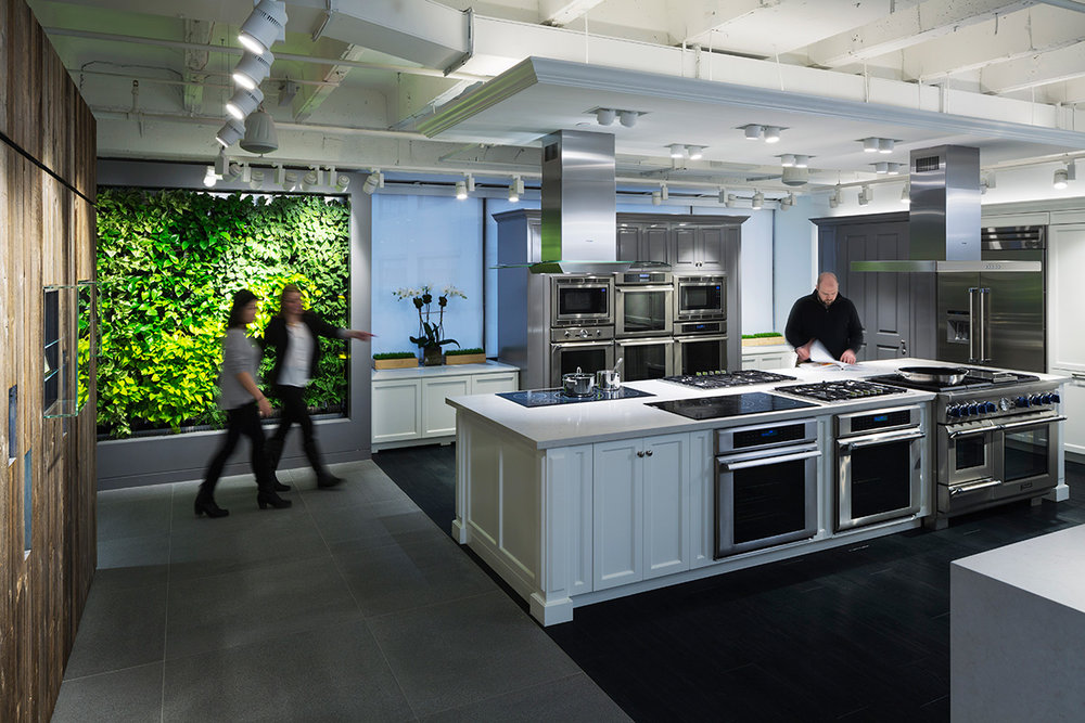 Two women walking by a green wall as a man reviews a catalogue in a display kitchen in the BSH Showroom in New York. MEP provided by 2LS Consulting Engineering.