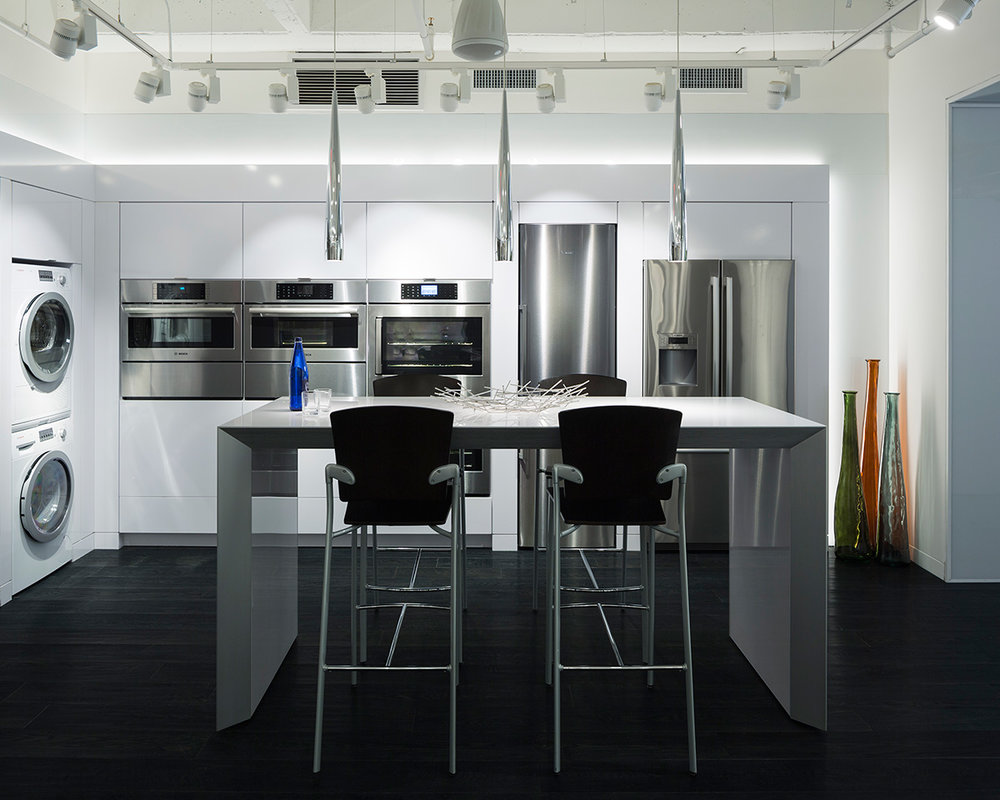 A modern, clean free standing kitchen island with bar seating and a display of fridges, ovens, washers and dryers in the BSH Showroom located in New York. MEP by 2LS Consulting Engineering.
