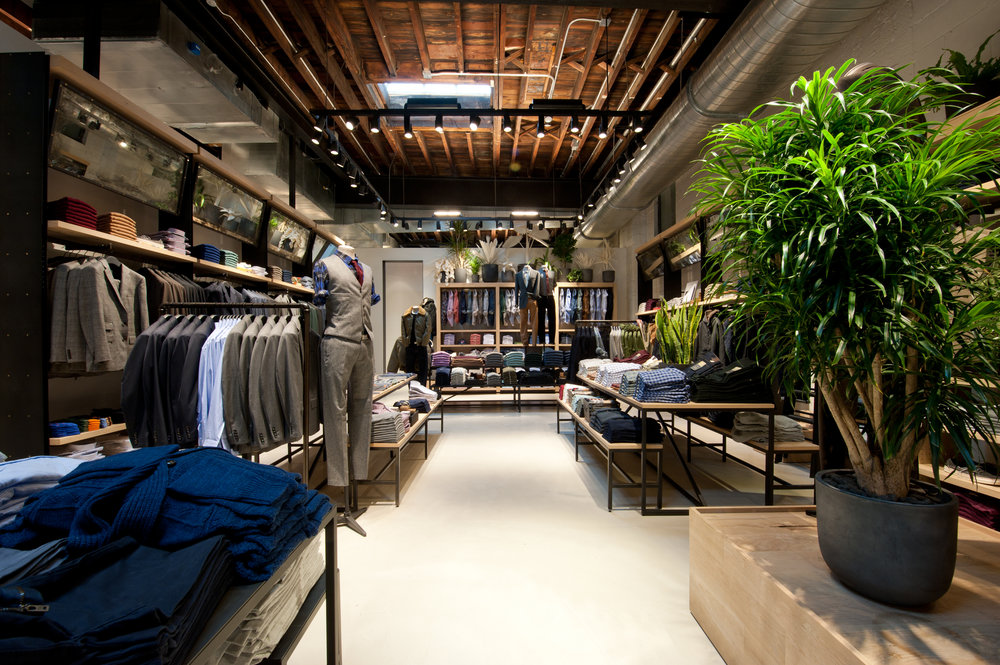 Blazers, dress shirts, and trousers on display in the contemporary design interior of J Crew Williamsburg, located in Brooklyn. MEP provided by 2LS Consulting Engineering.