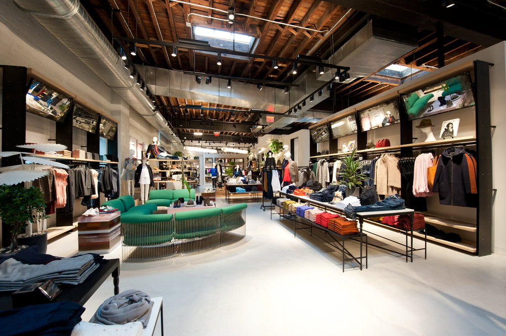 Green seating area surrounding a shoe display inside the retail space featuring stylish apparel in J Crew Williamsburg, Brooklyn, New York. MEP designed by 2LS Consulting Engineering.