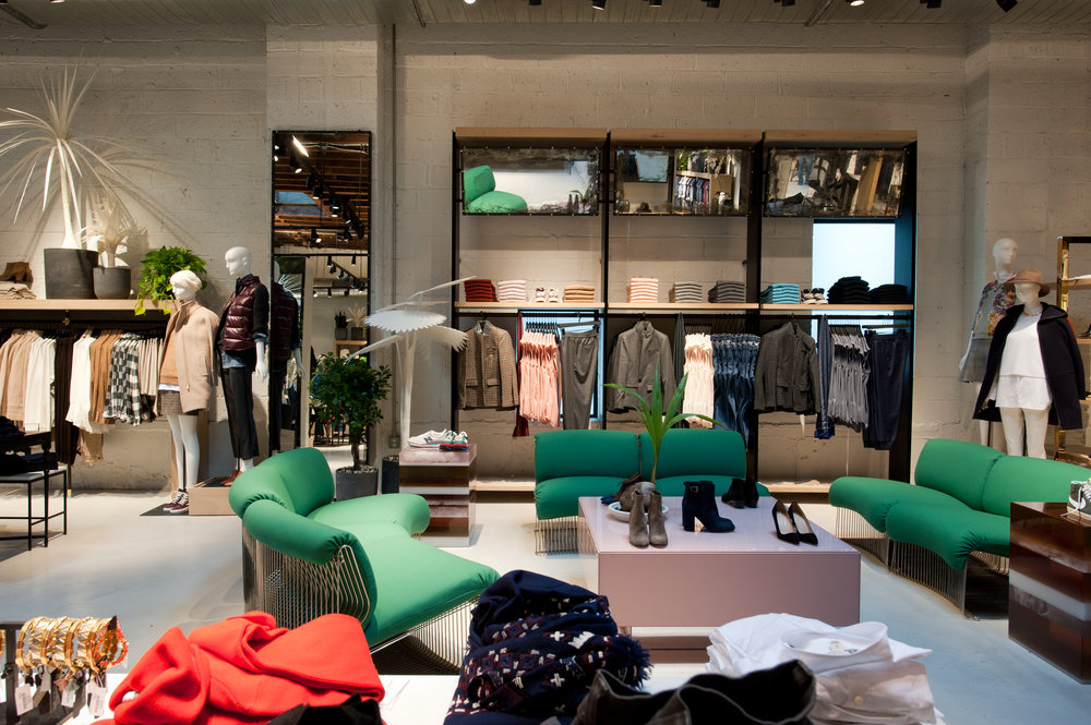 Womens shoes and accessories on display tables surrounded by manequins and display racks with clothing by American multi-brand, multi-channel, specialty retailer, J Crew. MEP by 2LS.