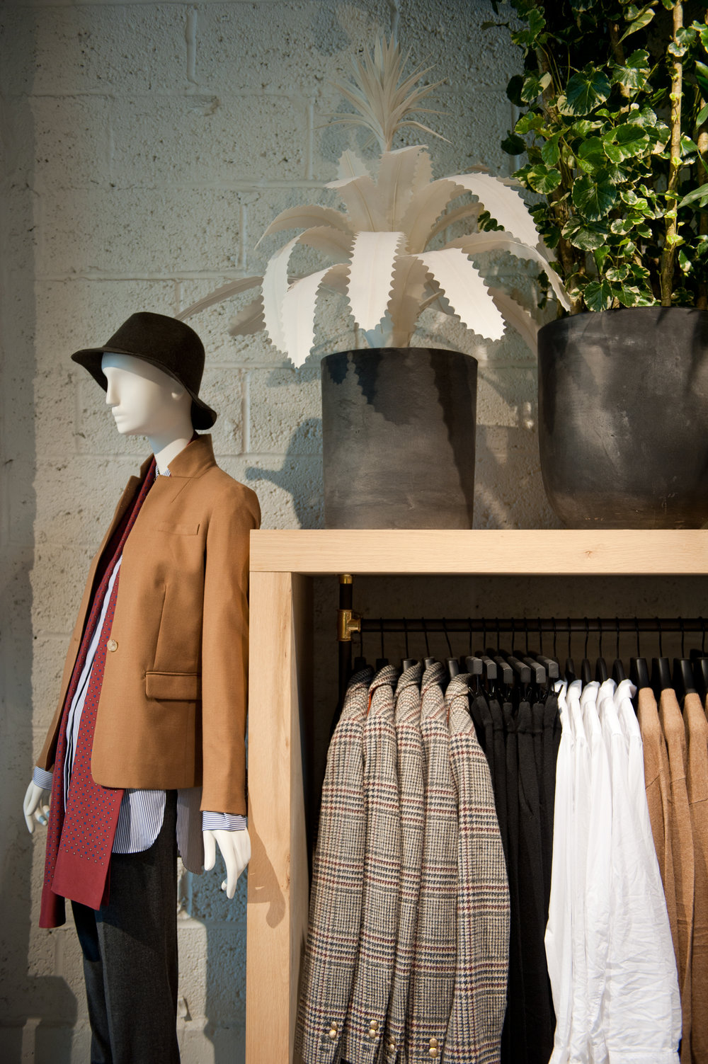 Mannequin wearing a bucket hat and a camel coat beside a display rack and fake plants in black pots. J Crew Williamsburg with MEP design by 2L Engineering.