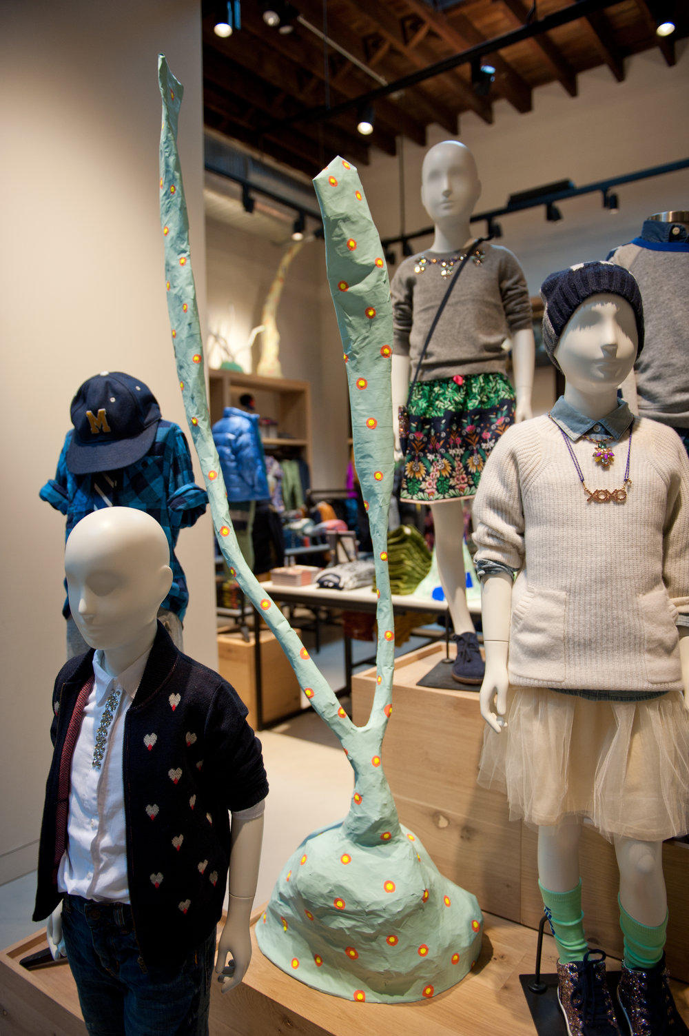 Mannequins of children wearing stylish clothes beside a whimsically painted branch in J Crew's Williamsburg location. MEP provided by 2LS Consulting Engineering.