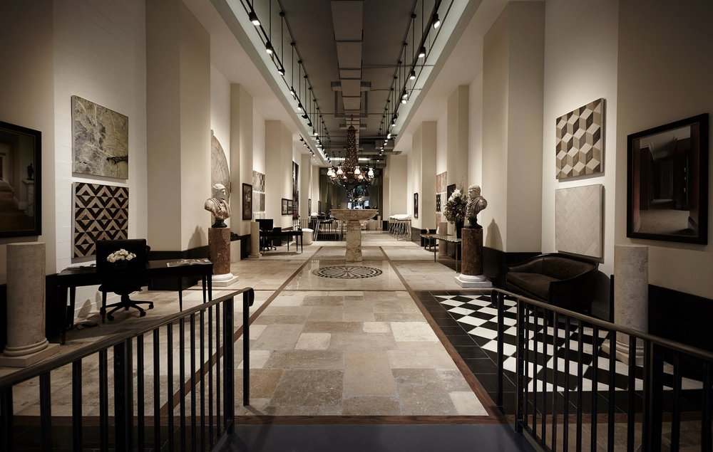 View of the interior of Lapicida, an international luxury natural stone and tile showroom, featuring tile samples and busts. MEP designed by New York based firm, 2L Engineering.