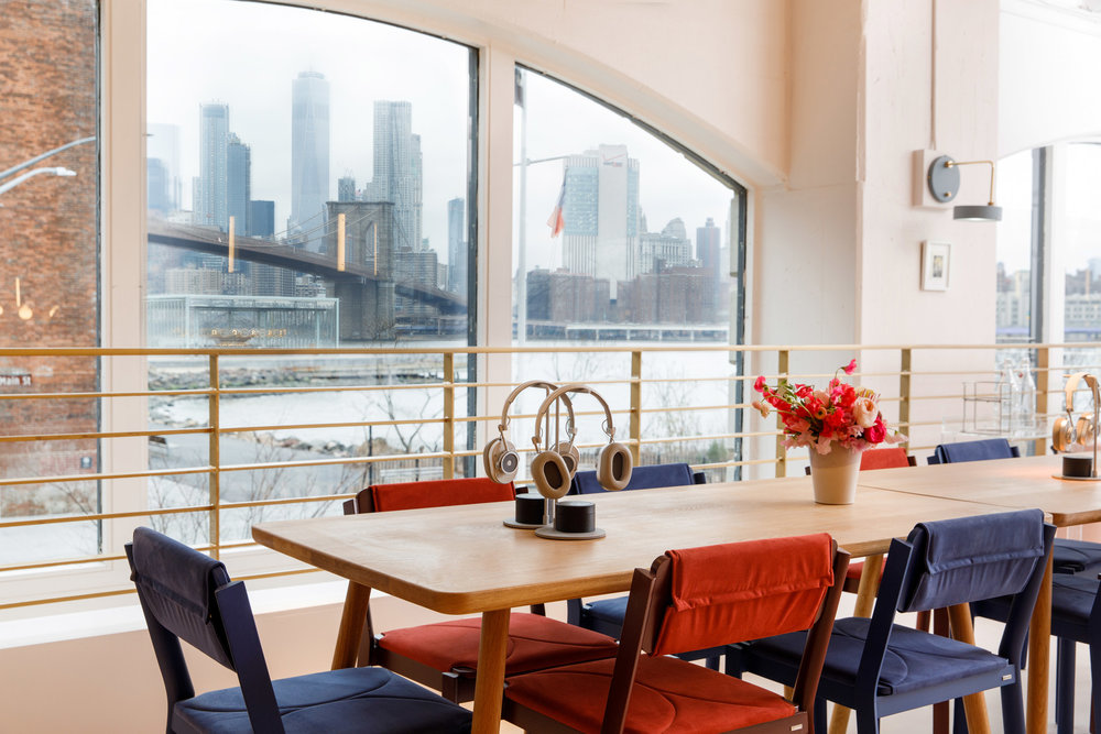 Headphones and flowers on a coworking table space in The Wing Dumbo, overlooking the Brooklyn Bridge and Manhattan skyline. MEP Engineering provided by 2L Engineering.