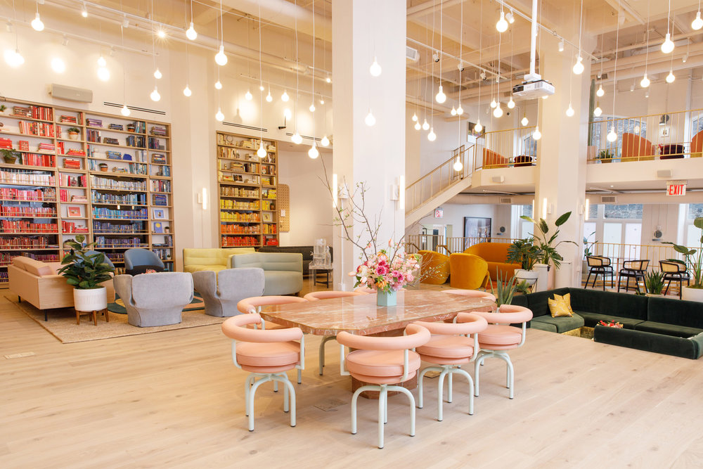 Hanging lightbulbs over an elaborate flower display tables with bookcases leading to private phone booths in The Wing Dumbo, Brooklyn. MEP Engineering provided by 2L Engineering.