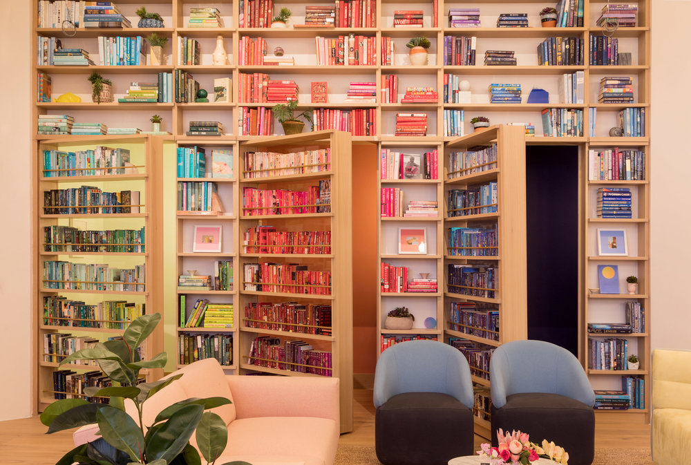 Bookcases organized by colors yellow, red, and blue, with secret openings leading to private phone booths in The Wing Dumbo, Brooklyn. MEP Engineering provided by 2L Engineering.