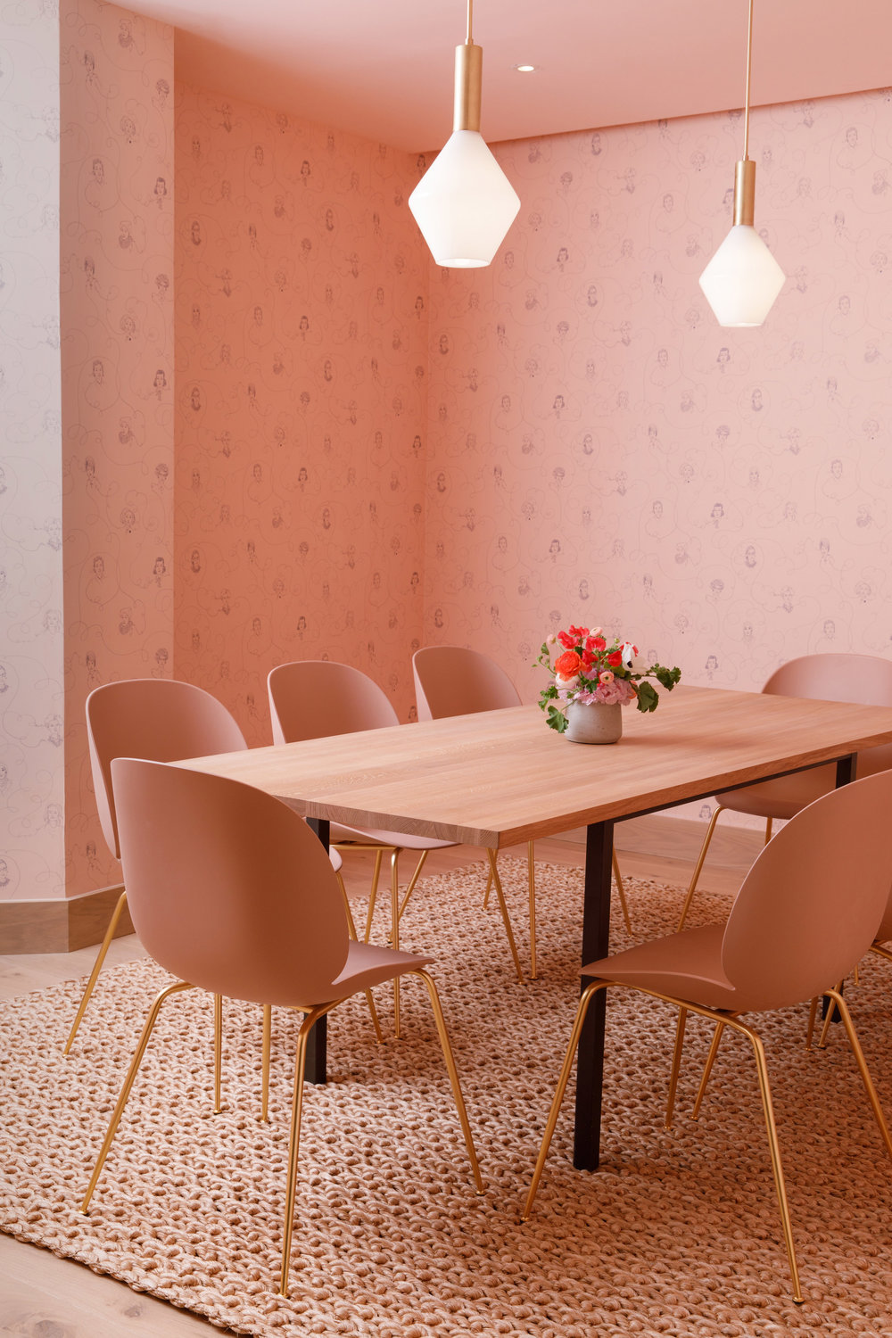 Pink accented private conference room area with famous women illustrated in a Victorian-era inspired wallpaper in The Wing Dumbo, Brooklyn. MEP Engineering designed by 2LS Consulting Engineering.