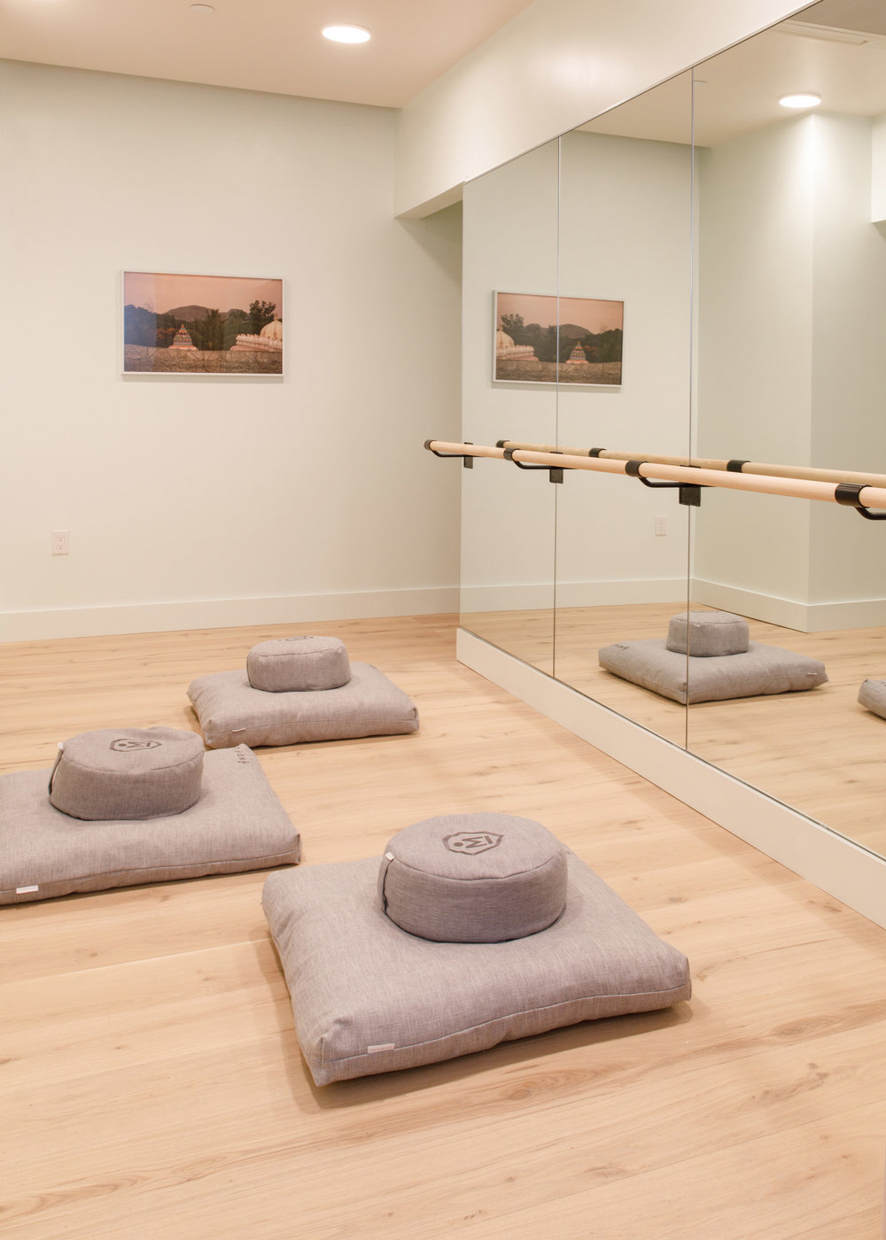 Yoga and barre studio with meditation pillows facing a mirror in The Wing Dumbo, Brooklyn. MEP Engineering designed by 2LS Consulting Engineering.