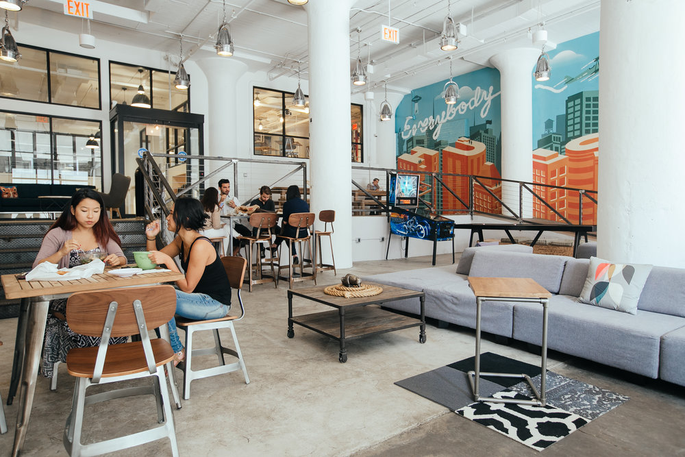People hanging out at the WeWork break area where they eat, play, and relax beside a colorful mural. MEP design by 2L Engineering.