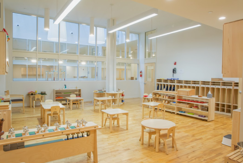 Classroom with wood accents such as wooden flooring, shelving units, tables, and chairs, in the Montessori School Flatiron. MEP designs provided by 2L Engineering.