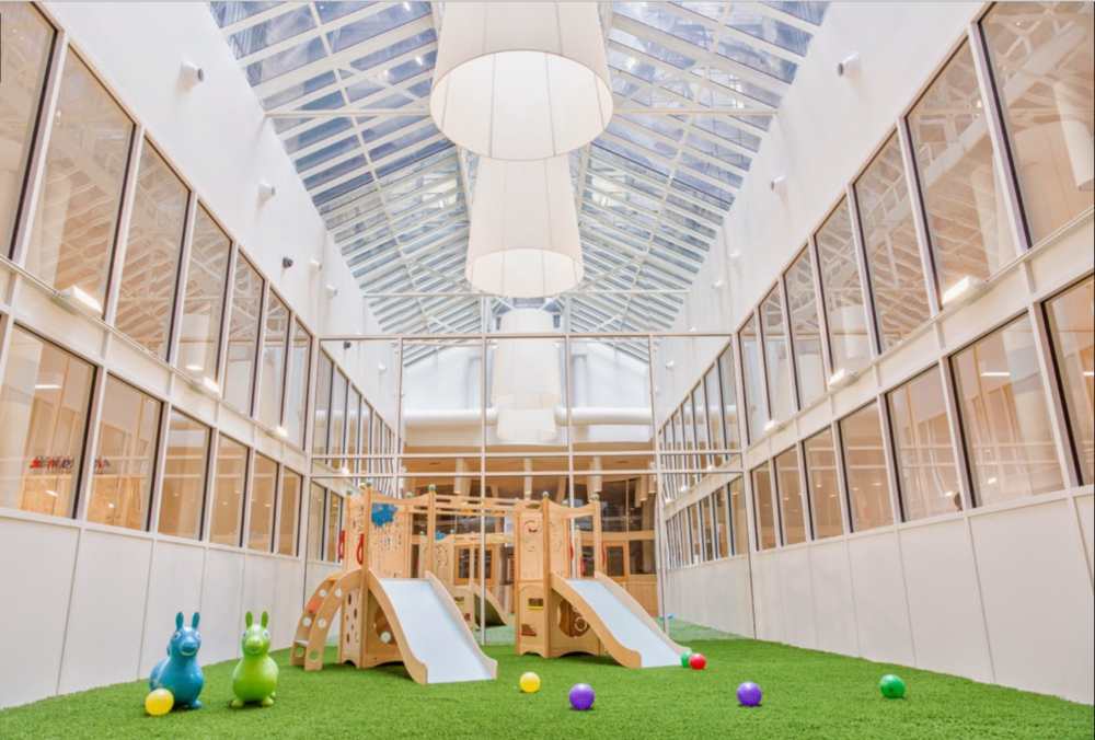 Brightly lit playroom with slides and an inside playground at the Flatiron location of the Montessori School. MEP Engineering provided by 2LS Consulting Engineering.