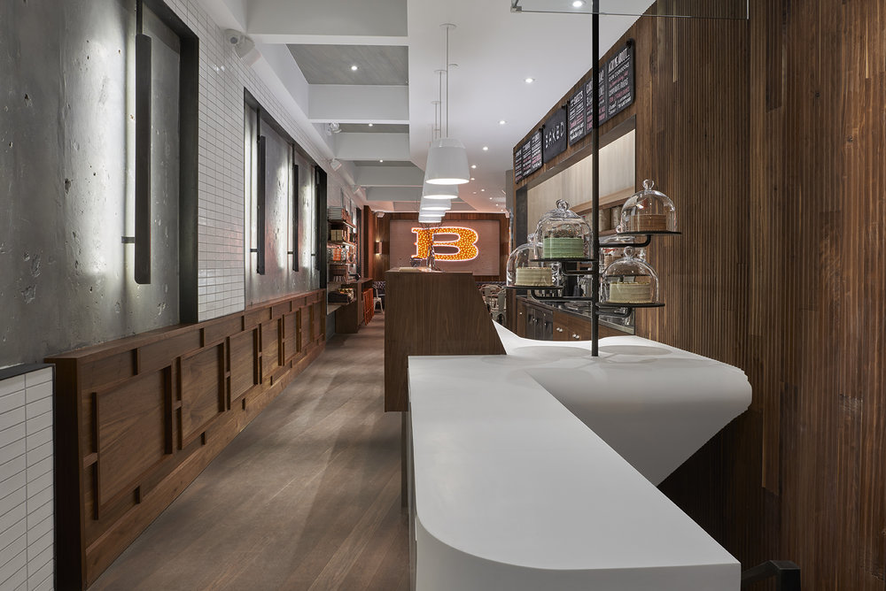 Alternate view of the counter and zone to place orders with a large illuminated B for Baked Tribeca, a bakery restaurant. MEP designed by 2LS Consulting Engineering firm.