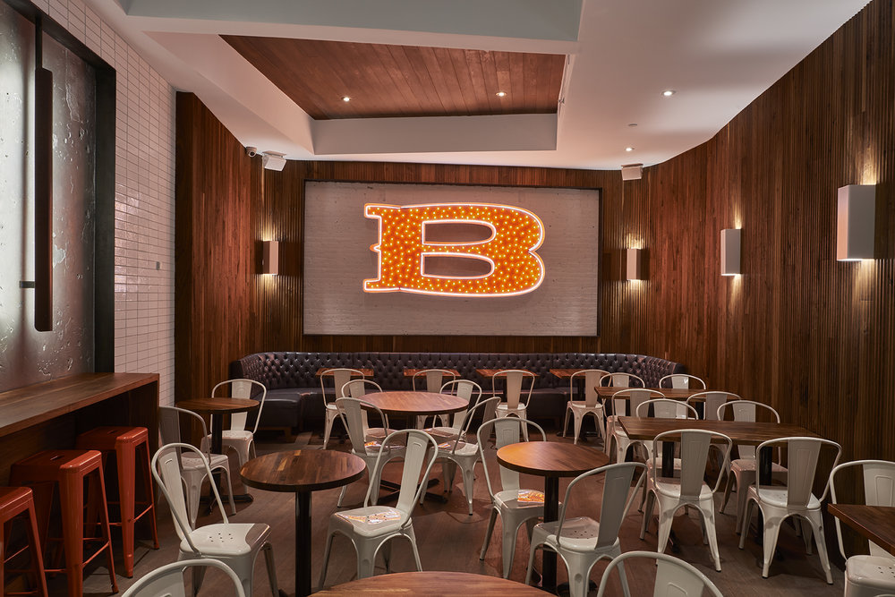 Large illuminated red B with yellow lights mounted on a white brick wall and surrounded by wooden lining over a seating area for customers at Baked Tribeca. MEP by 2LS Consulting Engineering.