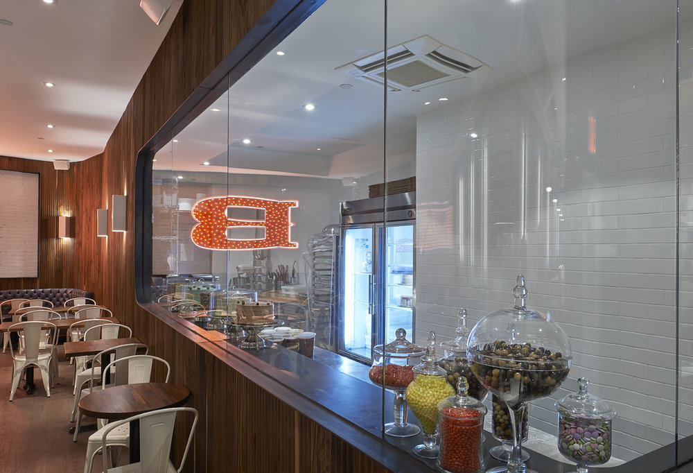 Viewing window on a wall composed of wooden lining, lending view to the kitchen area of Baked Tribeca with cakes in the fridge and candies in various jars. MEP by 2LS Consulting.