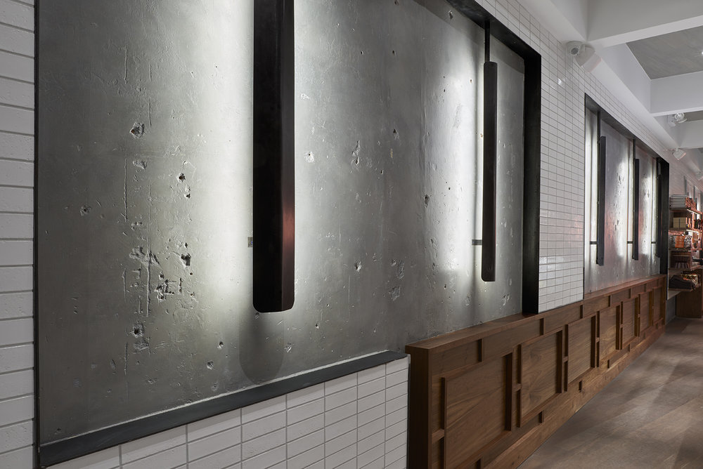 Wall of Baked Tribeca with multiple materials including: cement, ceramic tile, and wood. MEP designed by 2L Engineering, a New York firm.