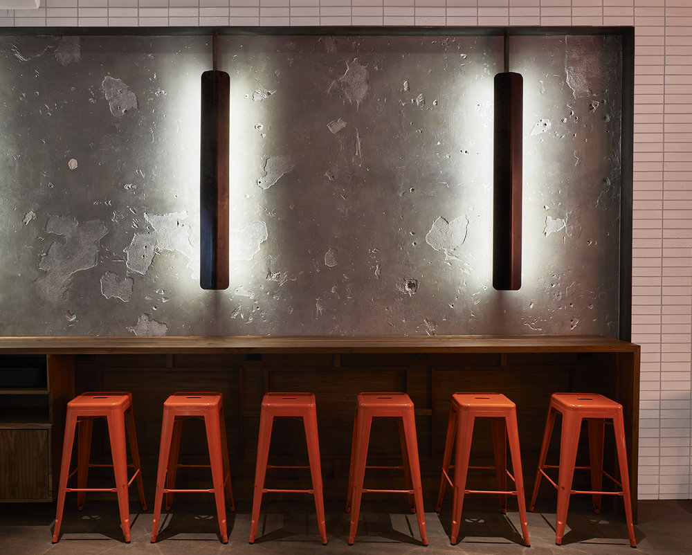 Dramatically lit concrete wall with scrapes and holes over a counter and orange stools in Baked, a bakery located in Tribeca. MEP designed by 2L Engineering, a New York Engineering firm.