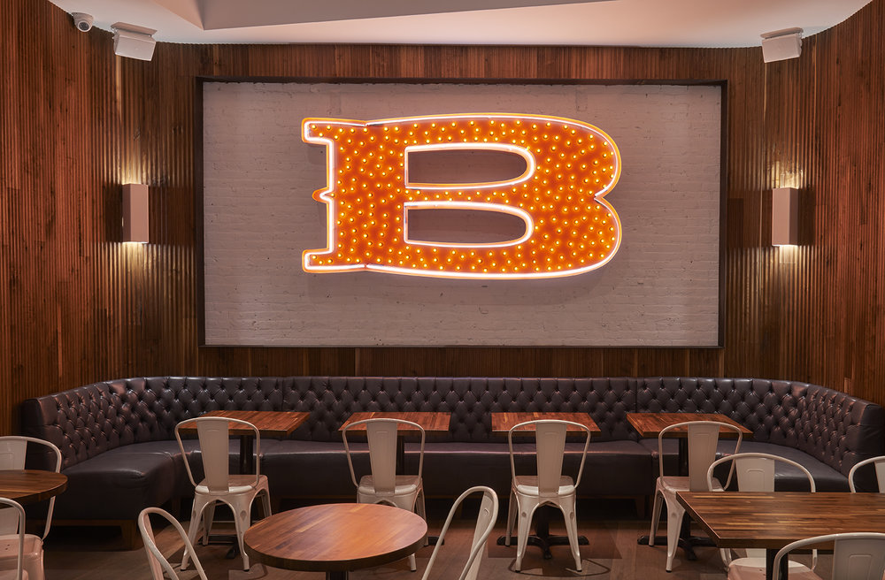 Bright B sign in red with yellow lights mounted on a white brick wall and hanging over the seating area of Baked Tribeca. MEP designed by 2LS Consulting Engineering.