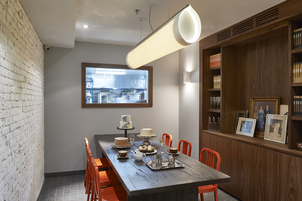 Private dining space in Baked Tribeca, with champagne, cakes, and pastries on the wooden table and a view into the kitchen. MEP provided by 2L Engineering.