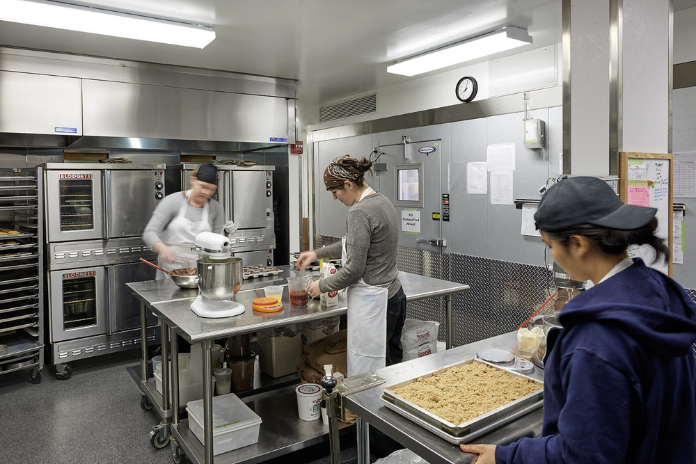 Three bakers preparing food in the kitchen of Baked, a bakery located in Tribeca. MEP designed by 2L Engineering, a New York based firm.