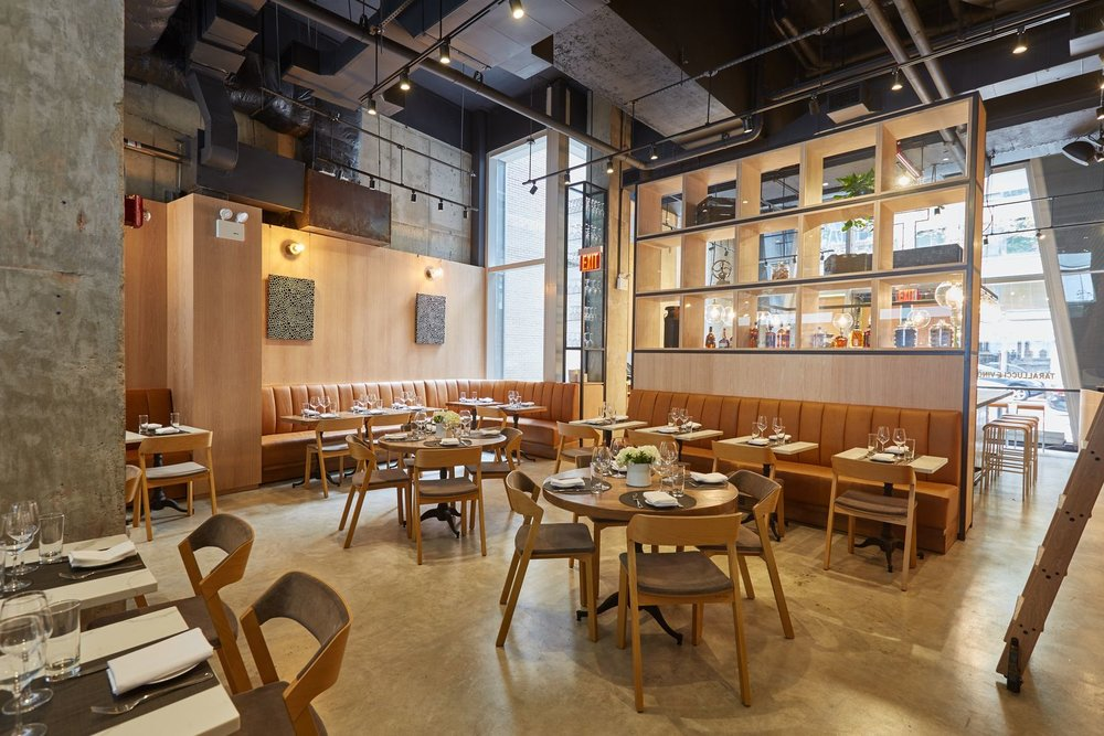 Indoor seating with warm tones and a large decorative shelf inside Tarallucci e Vino in New York. MEP provided by 2LS Consulting Engineering.