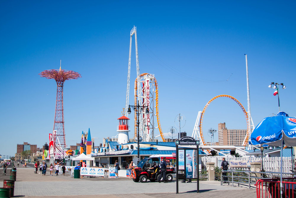 Wideshot view of Luna Park's ticket office, souvenir shop, and the Thunderbolt Rollercoaster in the distance on Coney Island, Brooklyn. MEP designed by 2L Engineering..